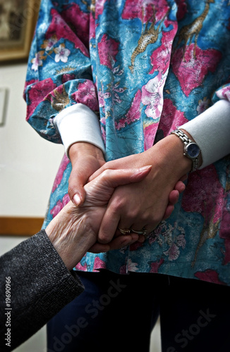 Nurse holding senior womans hand