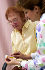 Nurse giving senior woman a bottle of pills