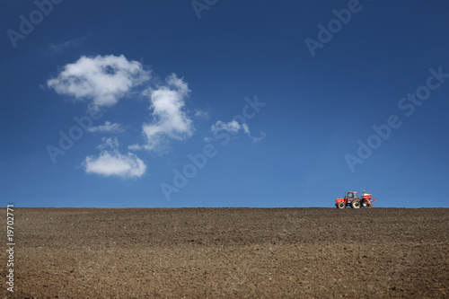 agricultural tractor cultivating on field