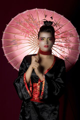 Sexy young geisha holding a painted umbrella
