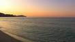 HD Gentle waves on a sandy beach in sunrise, rocks background