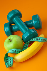 dumbells with measuring tape and fruits