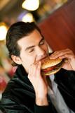 Man in restaurant eating hamburger poster