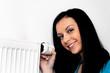 Frau mit Heizkörper und Thermostat einer Heizung