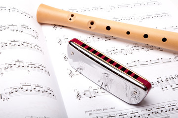 Mouth harmonica and wooden flute on sheet music. Close up.