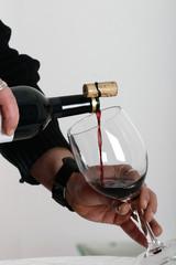 sommelier en train de verser du vin rouge dans un verre