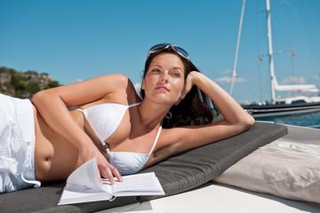 Attractive woman sunbathing on luxury boat