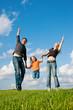 Familie springt auf Wiese im Sommer