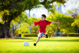 Fototapety Young excited boy kicking ball in the grass