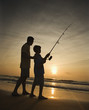 Man and young boy fishing in surf.