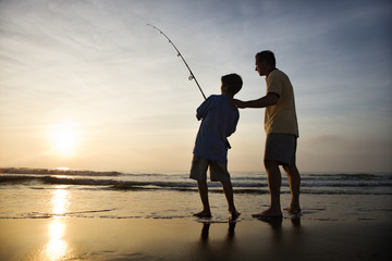 Man and young boy fishing in surf