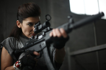 stylish woman holding an assault rifle