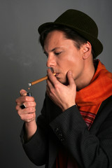 Stylish young man in hat gets a light cigar