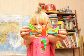 Girl shows colorful dragonfly