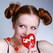 Portraite of smiling girl holding heart shaped lollipop