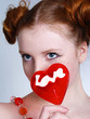 portrait of young redheaded woman with lollipop