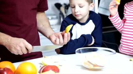 Dad Cutting Up Fruit for Children To Eat