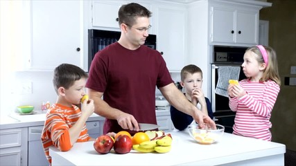Dad and Kids Eating Fruit Wide Shot