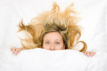 Teenager with wild hair in bed