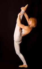 Gymnast in the bright stage costume performs tricks