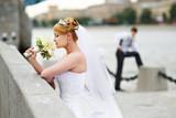 Groom adn bride for walk on embankment river poster