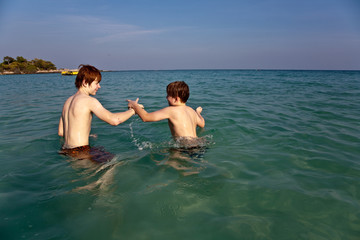 brothers are playing together in a beautiful sea