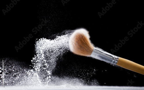 thick professional brush and loose white powder particles