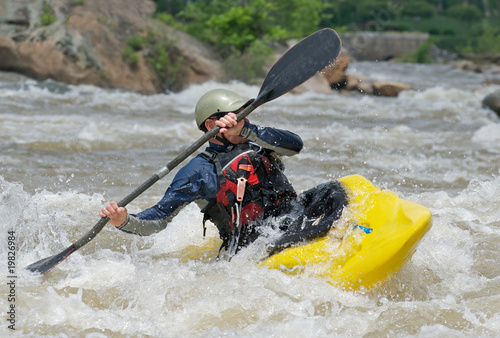 Kayaker fighting the rapids of a river.