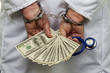 Doctor with dollar bank notes and handcuffs