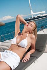 Blond woman sunbathing in bikini on luxury yacht