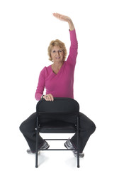 Senior woman doing arm stretch on chair