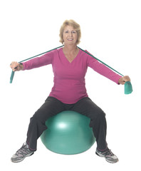 Senior woman exercising with ball and resistance band