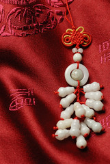 Traditional jade lucky knot on Jin-Silk background.