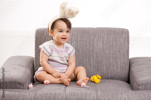 Baby girl with toy chicken and eggs