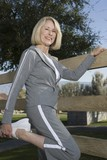 Mature woman stretches leg in warm up exercise