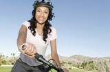 Woman in cycling helmet holds handlebars of mountainbike
