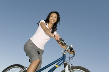Woman sits on mountain bike against clear blue sky