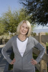 Mature adult woman stands smiling, in tracksuit with hands on hips