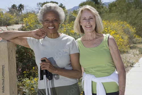 Senior women stand with walking poles
