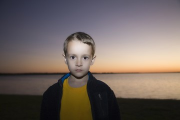 Boy stares at camera from sunset beach