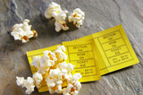 pair of ticket stubs with popcorn snack poster