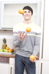 mann jongliert mit orangen