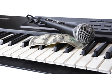 A microphone and dollar lying on the keys