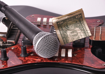 A microphone and dollar lying on a guitar