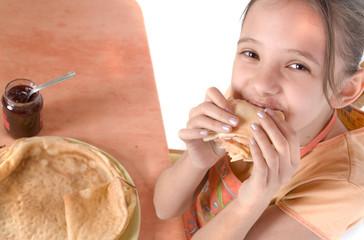enfant rieuse qui mange une crêpe - vue d'en haut