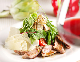 salad with pork, tomatoes and arugula on a white plate
