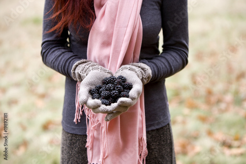 A young woman holding a handful of blackberries