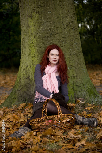 A young woman sitting beneath a tree with a picnic basket
