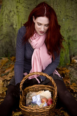 A young woman sitting beneath a tree, looking in picnic basket