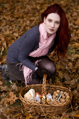 A young woman kneeling next to her picnic basket